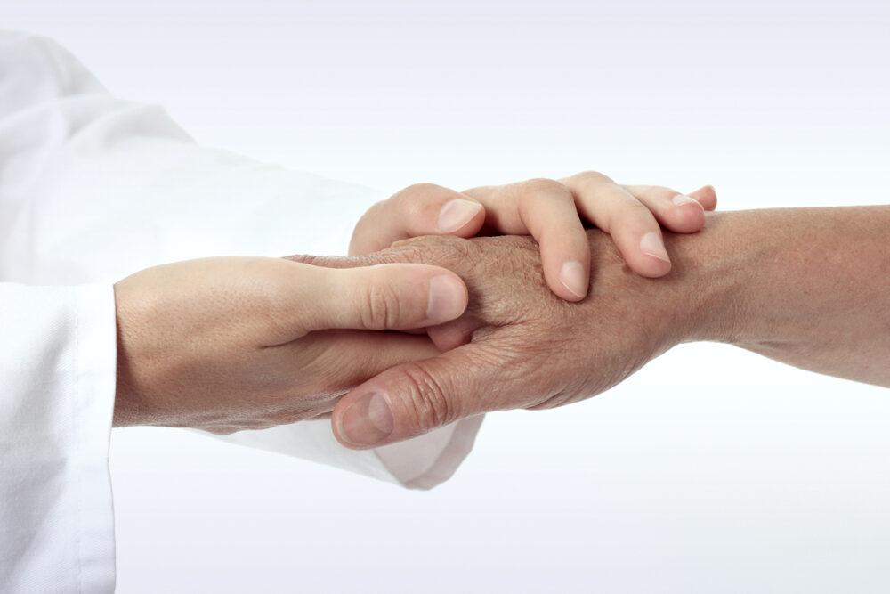 Pflegekraft hält die Hand eines älteren Person