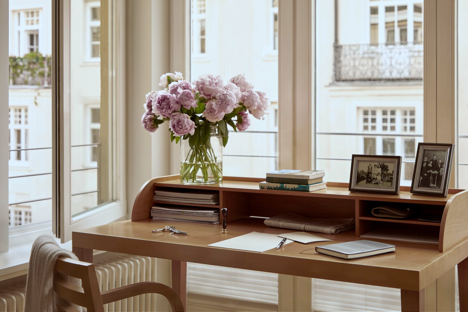 liebevoll dekorierte Schreibecke in einer Wohnung der Tertianum Residenz München mit Blick aus dem Fenster.
